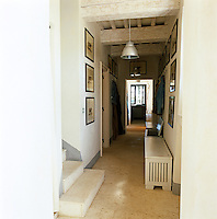 The entrance hall has a travertine floor and a whitewashed wooden beam ceiling