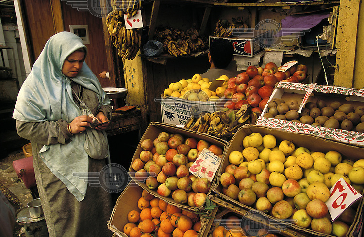 Woman counting out cash to buy fruit at a stall in the market behind Al-Azhar Mosque in the heart of the Islamic City..