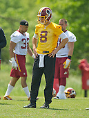 Washington Redskins quarterback Kirk Cousins (8) looks on as his teammates participate in an organized team activity (OTA) at Redskins Park in Ashburn, Virginia on Wednesday, May 25, 2015.<br /> Credit: Ron Sachs / CNP