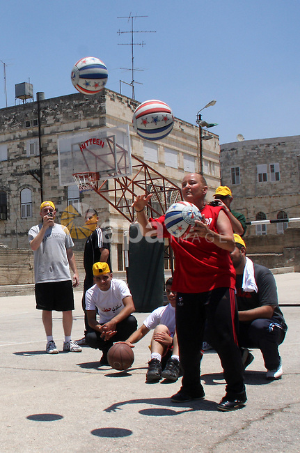 American basketball handler, Tanya Crevier shows a Palestinian children how to play a basketball in the West Bank city of Nablus,Thursday, June 10, 2010. Crevier, a former professional basketball player in the US, is on a 3-day visit to the West  Bank where she is performing and training Palestinian children. Photo by Wagdi Eshtayah