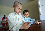 Nasratullah Ahmadzai, 4, and his brother Sanaullah, 2, play games on a phone in their home in Harrisonburg, Virginia. Refugees from Afghanistan, they were resettled in Harrisonburg by Church World Service.<br /> <br /> Photo by Paul Jeffrey for Church World Service.