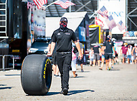 Jul 18, 2020; Clermont, Indiana, USA; A crew member rolls a Goodyear racing slick for the dragster of NHRA top fuel driver Doug Kalitta during qualifying for the Summernationals at Lucas Oil Raceway. Mandatory Credit: Mark J. Rebilas-USA TODAY Sports