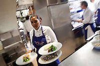 A waitress collects dishes from the kitchen at Jacques Maximin's restaurant Le Bistro de la Marine, Cagnes sur Mer, France, 07 April 2012