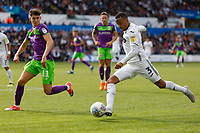 Martin Olsson of Swansea City (R) crosses the ball past Callum O'Dowda of Bristol City (L) during the Sky Bet Championship match between Swansea City and Bristol City at the Liberty Stadium, Swansea, Wales, UK. Saturday 25 August 2018