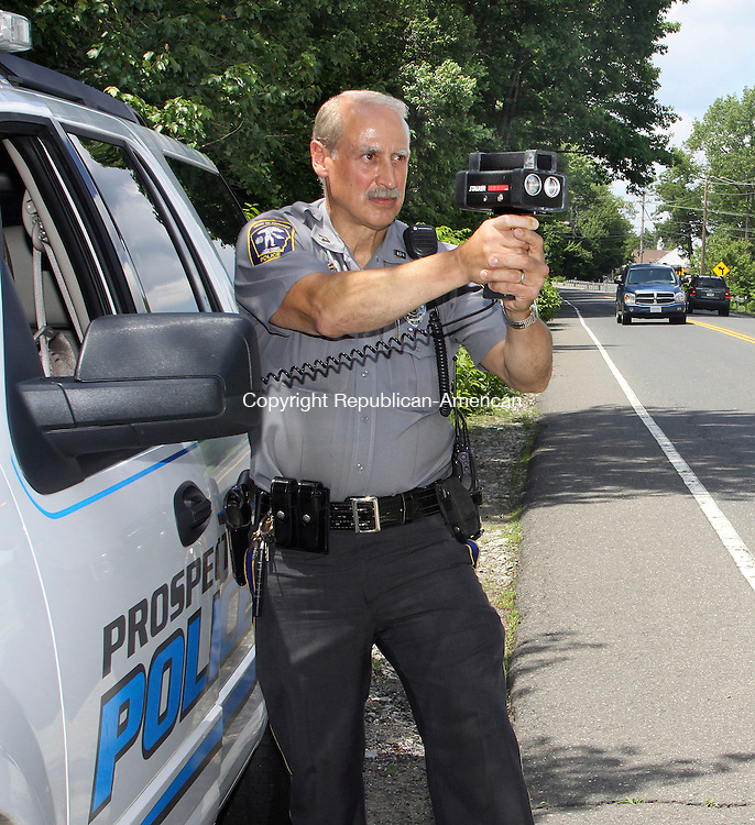 PROSPECT CT.-04 JUNE 2010-060410DA01-Prospect Police Officer Norm George holds a police speed laser gun on Rt 69 in Prospect Friday. A Police Assistance Intermunicipal Agreement among Prospect, Beacon Falls and Bethany is in the works. It will allow the towns to fill a private duty post from the other town if they can't fill it with one of their own. The towns modeled the agreement after one between Middlebury and Naugatuck. <br /> Republican-American  Darlene Douty