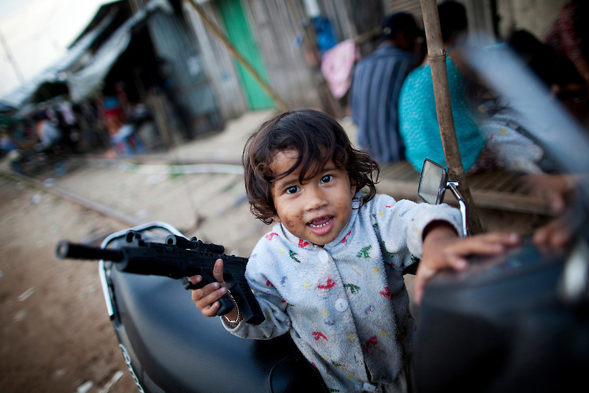 A child plays with a toy gun along the railway tracks in Phnom Penh's Tuol Kork district.