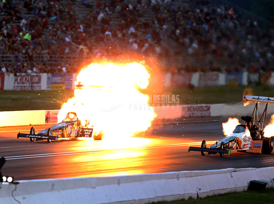 Jun 5, 2015; Englishtown, NJ, USA; NHRA top fuel dragster driver Morgan Lucas explodes an engine on fire alongside Clay Millican during qualifying for the Summernationals at Old Bridge Township Raceway Park. Mandatory Credit: Mark J. Rebilas-