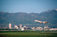 Continental Airlines jet taking off from Salt Lake city International Airport with Salt Lake City, Utah and the Wasatch Mountains in the background. cityscape, urban design, airplane. Salt Lake City Utah.