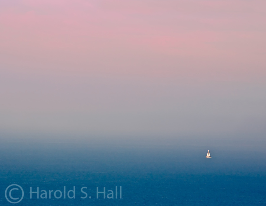 A lone sail boat on Lake Michigan in a haze makes it difficult to tell where the sky begins and the water ends.