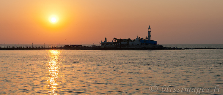 The sun begins to set creating pastel shades around Haji Ali Mosque in the Arabian Sea off Mumbai, India.
