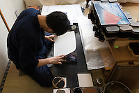 Printer Yoshio Kyoso places paper on a woodblock as he works on a reproduction of Katsushika Hokusai's Fine Wind, Clear Morning. Adachi Foundation for the Preservation of Woodcut Printing, Tokyo, Japan, July 15, 2014. The Foundation works to preserve the original techniques of Japanese woodblock printing. As well as recreating classic ukiyo-e from the Edo period, they train and employ young artisans, and also educate about the art form.
