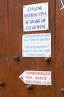 Winery with self service selling buying of the wine. Warning sign saying Be Aware (beware) of Clear Wine Wine With Sediment Tells us That the Wine is From Grapes... Potmje village, Dingac wine region, Peljesac peninsula. Dingac village and region. Peljesac peninsula. Dalmatian Coast, Croatia, Europe.