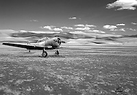 A vintage South African WWII airplane on a desert plain.