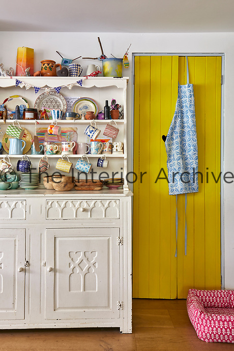 Vibrant colours and patterns feature in the kitchen. A painted dresser displays a collection of tableware.