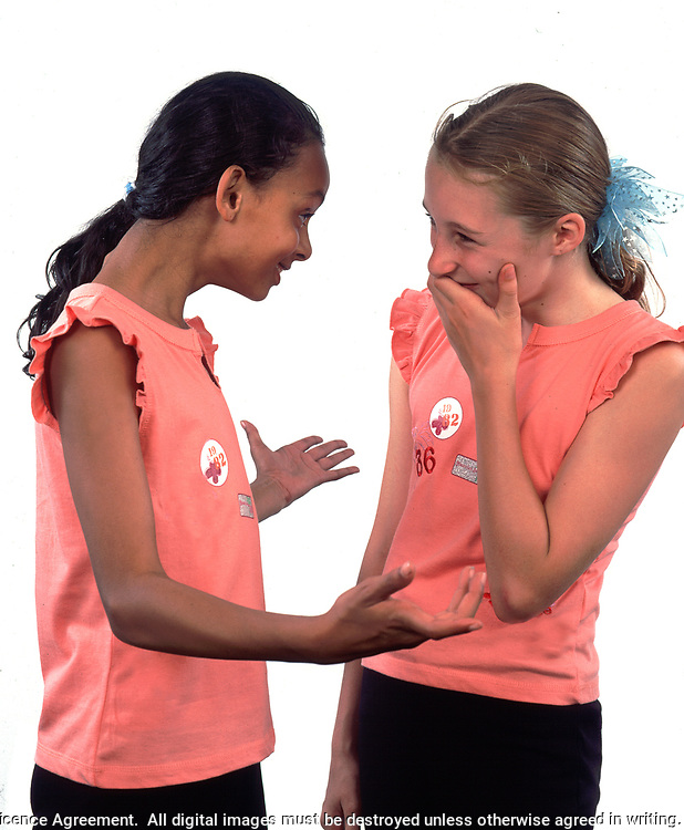 Two girls laughing together because they are wearing the same t-shirt, UK, studio, model release, 10-11 years old