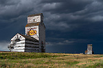 Abandoned grain elevator in rural Saskatchewan with a storm behind it creating a dramatic, awe inpsiring scene.