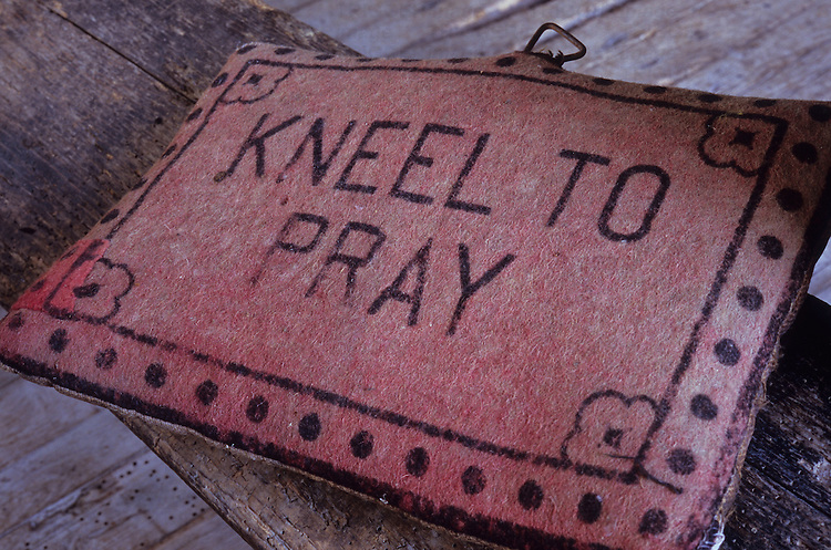 Vintage church kneeler made from stuffed pale red felt with printed message stating Kneel To Pray lying on wooden board