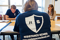 """Sam Carson (left), 28, a Master in Public Policy graduate student at Harvard, leads the Resistance School logistics group volunteer meeting before a session of Resistance School in the Taubman Building of Harvard University's John F. Kennedy School of Government, on Thurs., April 27, 2017. Also seen here are volunteer Liz Hanson (foreground), 28, and Molly Osborne (right), 27, both Master in Public Policy grad students at Harvard. The goal of the meeting was to plan how to direct attendees from the registration location to the lecture location. Resistance School was started by progressive graduate students at Harvard after the Nov. 8, 2016, election of President Donald Trump. Resistance School describes itself as a """"practical training program that will sharpen the tools [needed] to fight back at the federal, state, and local levels."""" Resistance School puts on live lectures by leading progressives that are streamed and archived online alongside other information on the Resistance School website. During the lectures, teams of volunteers engage with followers on social media, including Facebook and twitter, sharing soundbytes, quotations, and supplementary materials as the lectures happen."""