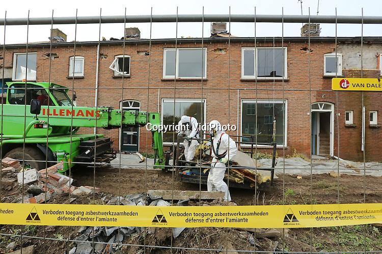 Foto: VidiPhoto<br /> <br /> HUISSEN - Specialisten van de Brabantse asbestverwijderaar ABP, verwijderen woensdag asbest van de daken van 77 rijtjeshuizen in het Gelderse Huissen. De asbestplaten en -resten die gebruikt werden voor brandwering en isolatie, moeten eerst weg voordat de sterk verouderde woningen gesloopt kunnen worden. Op die plek bouwt woningbouworganisatie Waardwonen er 112 woningen voor terug, een mix van appartementen en eengezinswoningen. De sloop moest eerder al uitgesteld worden vanwege de aanwezigheid van vleermuizen in de spouwmuren. Het verwijderen van de asbest moet eind deze week gereed zijn.