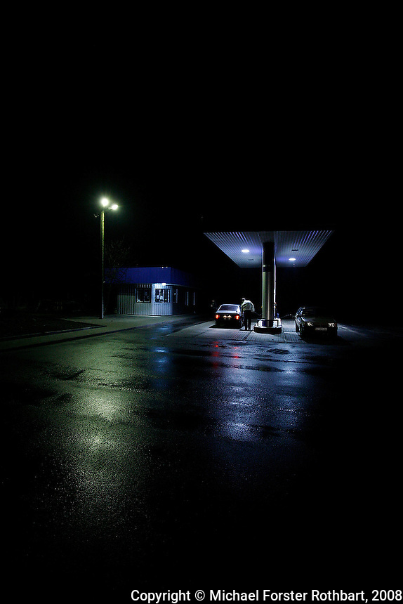 Customers fill their gas tanks at the Energiya Plus gas station at the edge of Ivankiv, Ukraine, the last 24-hour gas station on the road to the Chernobyl Exclusion Zone.  <br /> ------------------- <br /> This photograph is part of Michael Forster Rothbart's After Chernobyl documentary photography project.<br /> © Michael Forster Rothbart 2007-2010.<br /> www.afterchernobyl.com<br /> www.mfrphoto.com <br /> 607-267-4893 o 607-432-5984<br /> 5 Draper St, Oneonta, NY 13820<br /> 86 Three Mile Pond Rd, Vassalboro, ME 04989<br /> info@mfrphoto.com<br /> Photo by: Michael Forster Rothbart<br /> Date: 11/2008    File#:  Canon 5D digital camera frame 52871 <br /> ------------------- <br /> Original caption: .Customers fill their gas tanks at the Energiya Plus gas station at the edge of Ivankiv, on the road to Sukachi. (In this photo I was trying to capture a sense of isolation and the darkness of the 15-hour night.).