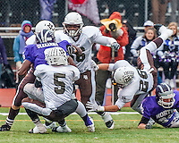 Mt. Carmel defenders converge on Downers Grove's Richard Olekanma for a  loss in the second quarter of Saturday's game