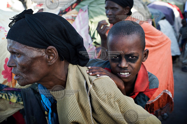 A woman carries a sick child at an IDP (internally displaced persons) camp in Mogadishu. The people staying here fled famine in South Somalia.