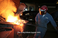 Ramiro Delgado works to remove impurities from the 10,000 pounds of melting scrap iron at D & L Foundry in Moses Lake, Washington on August 16, 2006. The factory produces iron manhole covers. His gloves and protective suit are designed to insulate his hands, lower arms and body from temperature extremes and hot splashes fro molten metals or other hot liquids. His Class B hard hat and face shield protect him from flying or falling objects, and from electrical hazards with high-voltage shock and burn protection up to 20,000 volts.