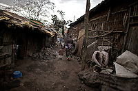 Mother and daughter walk though the neighborhood where they live, where commercial sex workers like herself wait for clients, in the center of the city of Bahir Dar, in Nothern Ethiopia on March 4, 2009. Most of the women living there were formerly sold into marriage as children by their families in their villages, in rural areas surrounding the city.  ..Names of subjects have been fictionalized and specific locations have been omitted to protect the identities of the children portrayed in the story.