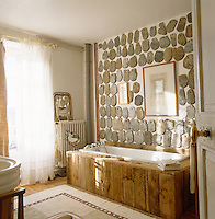 The wall above this rustic wood-clad bath is decorated with stone roof tiles