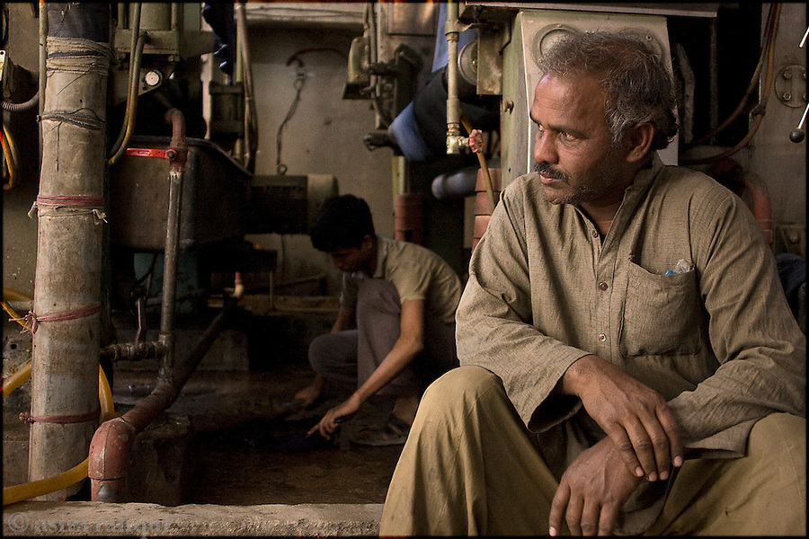 at a garment factory in karachi - a day wage worker and young apprentice