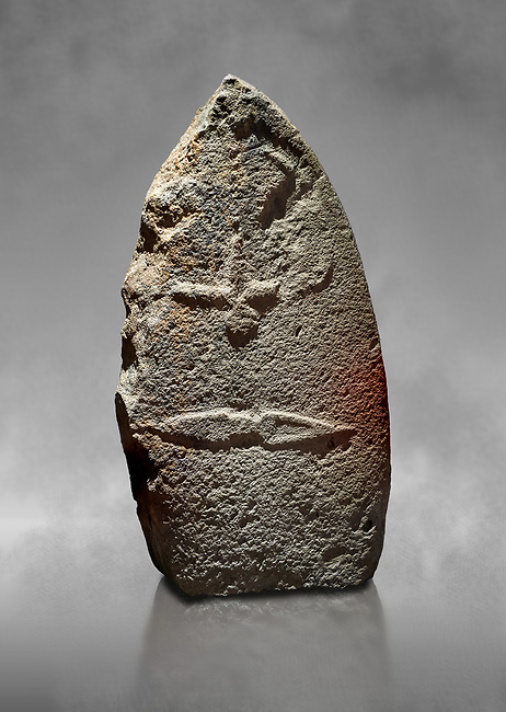Late European Neolithic prehistoric Menhir standing stone with carvings on its face side. The representation of a stylalised male figure starts at the top with a long nose from which 2 eyebrows arch around the top of the stone. below this is a carving of a falling figure with head at the bottom and 2 curved arms encircling a body above. at the bottom is a carving of a dagger running horizontally across the menhir. the bottom is a carving of a dagger running horizontally across the menhir. Excavated from Piscina 'E Sali VI site,  Laconi.  Menhir Museum, Museo della Statuaria Prehistorica in Sardegna, Museum of Prehoistoric Sardinian Statues, Palazzo Aymerich, Laconi, Sardinia, Italy