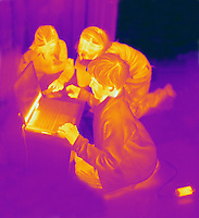 Thermogram of children and a computer.  The different colors represent different temperatures on the object. The lightest colors are the hottest temperatures, while the darker colors represent a cooler temperature.  Thermography uses special cameras that can detect light in the far-infrared range of the electromagnetic spectrum (900?14,000 nanometers or 0.9?14 µm) and creates an  image of the objects temperature..