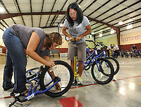 NWA Democrat-Gazette/ANDY SHUPE<br /> Amy Brown (left) and May Clevenger, both parents and volunteers, inflate a tire on a bike Friday, Sept. 11, 2015, while assembling a bicycle at John Tyson Elementary School in Springdale. Volunteers assembled the last 32 bikes of a total 850 bikes funded by a grant from the Walton Family Foundation.
