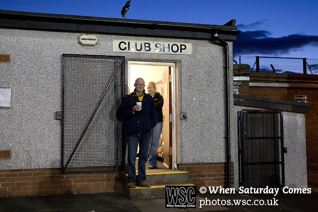 Two Alloa Athletic football supporters watching their team from outside the club shop at Recreation Park during the Co-operative Insurance Cup second round match with visitors Aberdeen. Scottish League second division Alloa lost the match by three goals to nil against their Premier League rivals in a match watched by 1649 spectators.
