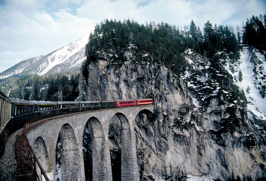 Winter scene. A view of the a curving bridge and the front of the train as it travels into a tunnel. Seen from the windows of the famous Glacier Express train which travels from St. Moritz to Zermatt, Switzerland. ST. Moritz, Switzerland.