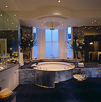 A Hollywood-style bathroom complete with circular Jacuzzi clad in dark blue tiles and a dark blue deep pile carpet