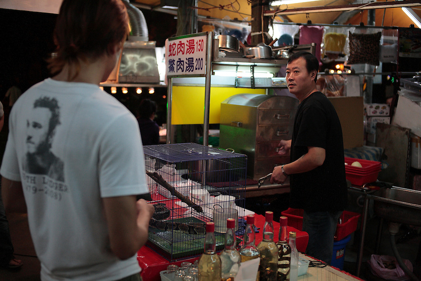 A young man is ordering a snake soup (150 Taiwan dollars = 6 USD) in restaurant of night market of Taipeh.