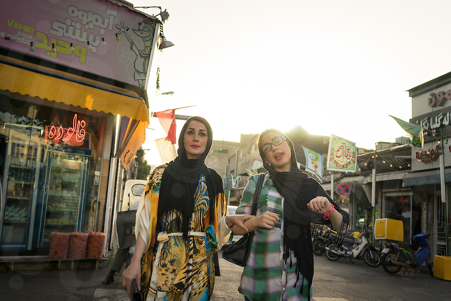 June 12, 2014 - Tehran, Iran. Two young girls walk in the streets of Tehran. Iranian women are increasingly reluctant to comply with government-imposed traditional dress codes and many have started to go around the prohibitions, wearing western-style hi jabs, made of fashionable fabrics. © Thomas Cristofoletti / Ruom