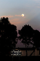 The nearly full moon rising  over the scoreboard at a neighborhood Little League ball park.