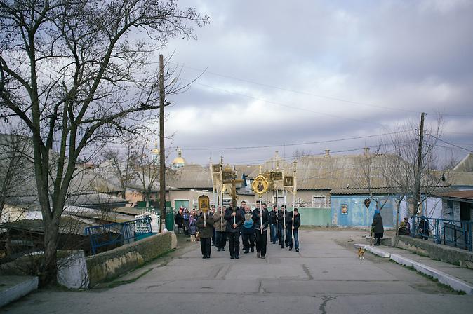 Prozession auf den Stra&szlig;en / Procession in the streets<br /><br />Vylkovo ist eine kleine Stadt im ukrainischen Teil des Donaudeltas im Oblast Odessa, in unmittelbarer N&auml;he zur rum&auml;nischen Grenze. Im 18. Jahrhundert siedelten hier Altgl&auml;ubige und Donkosaken, die im Zarenreich religi&ouml;s und politisch verfolgt wurden. Noch heute, 300 Jahre nach dem Exodos, versucht die Gemeinschaft ihre Traditionen, ihren Glauben und ihren Lebensstil zu bewahren und in die globalisierte Welt des 21. Jahrhunderts zu retten. / Vylkovo is a small town in the Ukrainian part of the Danube Delta, Oblast Odessa, close to the Rumanian border. In the 18th century during the Russian Empire, Old believers and Don Cossacks who had been persecuted for political and religious reasons. Until today, 300 years later, they try to preserve their traditions.