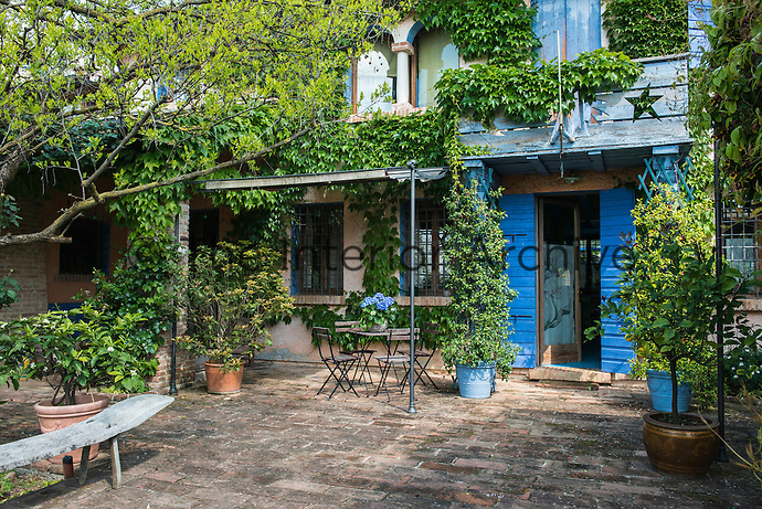 The facade of this picturesque house in Asolo is overgrown with Virginia creeper, the green leaves contrasting with the vibrant blue of the door shutters