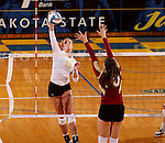 BROOKINGS, SD - OCTOBER 3:  Emily Veldman #12 from South Dakota State University looks to get a kill past Moni Corrujedo #10 from Denver in the second game of their match Friday night at Frost Arena. (Photo/Dave Eggen/Inertia)