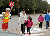 NWA Democrat-Gazette/DAVID GOTTSCHALK Dale Duerr, physical education teacher at Walker Elementary School, helps Wednesday, October 10, 2018, monitor the crosswalk as Haley Holt walks her daughter Sydney, a first grade student, to the school in Springdale. Walker Elementary School participated in National Walk to School Day. Studies have shown that walking to school positively influences academic achievement, student morning energy levels, attention, truancy, and absenteeism.
