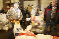 Wednesday, February 13, 2013.  Volunteer John Hooley carries a bag of musher's food to the appropriate  stack at Airland Transport in Anchorage.  Iditarod 2013