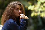 Candid natural portrait of a young woman with long curly brown hair and tranquil thoughtul expression on her face in fall nature scenery