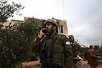 A member of the Israeli military speaks on the phone as others investigate the attack on the Hamayel home, that was burnt by suspected Jewish extremists using petrol bombs, in the village of Abu Falah, northeast of Ramallah, on November 23, 2014. Suspected Jewish extremists firebombed a house in a Palestinian village in the occupied West Bank early, its mayor told AFP, pointing the finger of blame at local settlers. Masud Abu Mura, mayor of Khirbet Abu Falah, said four women were inside the house at the time, but they all escaped unharmed. Photo by Shadi Hatem
