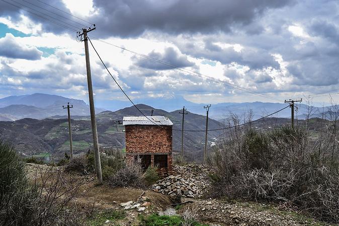 Transformatorenhäuschen, Pashtresh, Shpati, 2013, Strom wird  in Albanien hauptsächlich aus Wasserkraft gewonnen. Zu kommunistischen Zeiten wurde das Land elektrifiziert. Die Infrastruktur kann aber mit dem hohen Verbrauch heutzutage nicht mithalten
