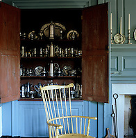 A built-in cupboard displays a collection of pewter and silverware in the dining room