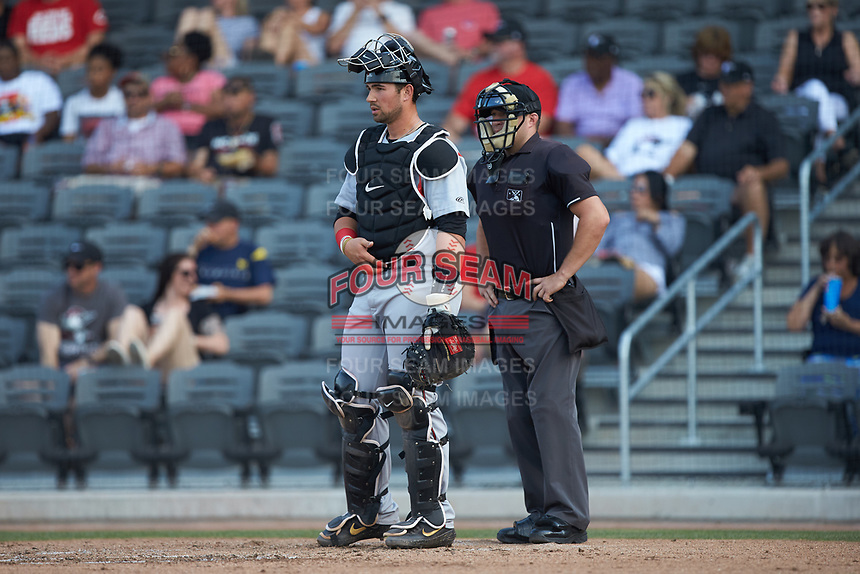 Carolina Mudcats catcher Payton Henry (15) and home plate umpire Jake Bruner during the game against the Fayetteville Woodpeckers at SEGRA Stadium on May 18, 2019 in Fayetteville, North Carolina. The Mudcats defeated the Woodpeckers 6-4. (Brian Westerholt/Four Seam Images)