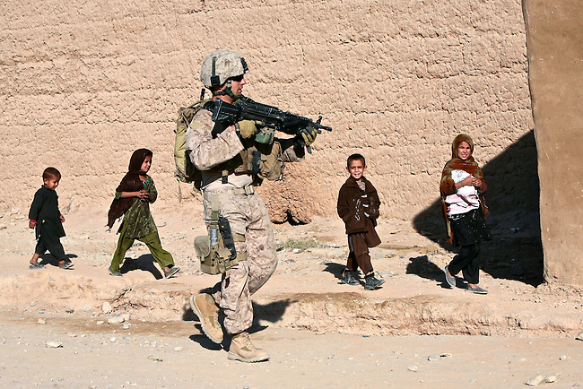 Children follow a U.S. Marine from Company I, 3rd Battalion, 4th Marine Regiment during a patrol in the town of Delaram, in western Afghanistan's Farah province. Children frequently tag along with the Marines on patrol, asking for pens, candy and other small items. Nov. 8, 2009. DREW BROWN/STARS AND STRIPES